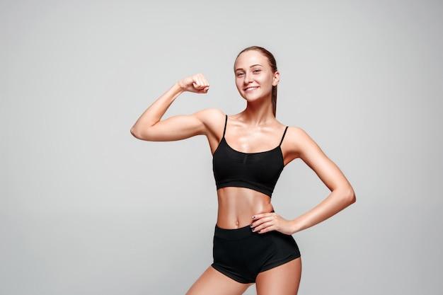 灰色のポーズ筋肉の若い女性アスリート 無料写真
