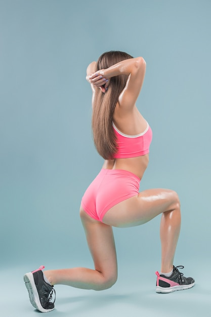 Muscular young woman athlete posing at studio on blue background Free Photo