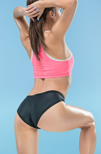 Muscular young woman athlete posing at studio on blue Free Photo