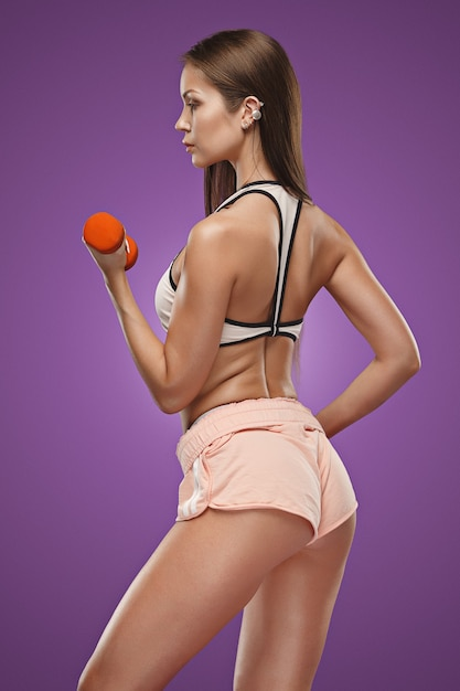 Muscular young woman athlete posing at studio on lilac background with dumbbells Free Photo