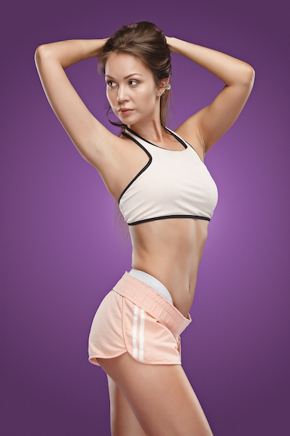 Muscular young woman athlete posing at studio on lilac background Free Photo