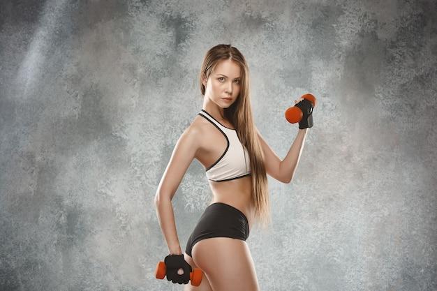 Atleta giovane donna muscolare che propone allo studio con manubri Foto Gratuite