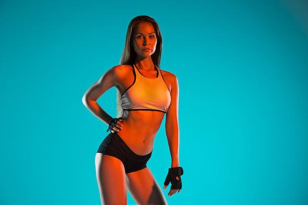ポーズ筋肉の若い女性アスリート 無料写真