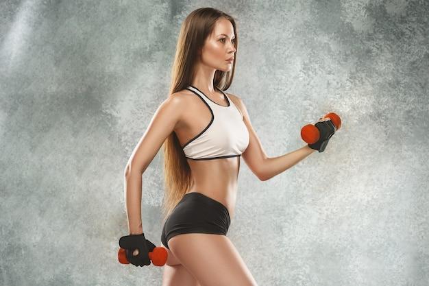 Atleta giovane donna muscolare in posa Foto Gratuite
