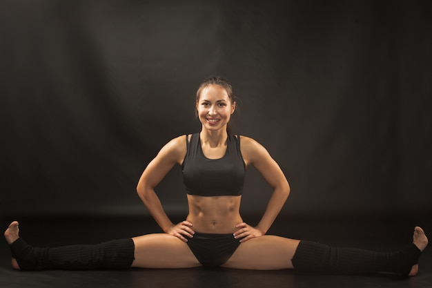 Muscular young woman athlete sitting in the split on black Free Photo