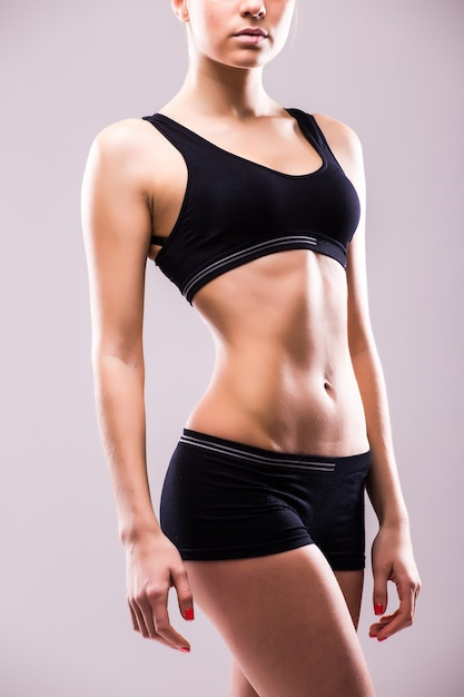 灰色の壁に腰に手を当てて見下ろして立っている筋肉の若い女性アスリート 無料写真