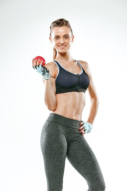 Мускулистый спортсмен молодой женщины стоя на белой предпосылке с яблоком. Бесплатные Фотографии