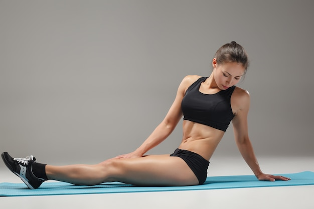 Muscular young woman athlete stretching Free Photo