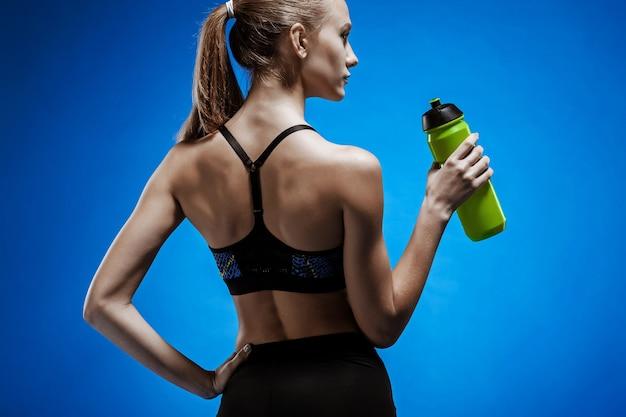 青の水で筋肉の若い女性アスリート 無料写真