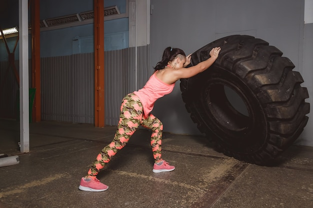 Muscular young woman flipping tire at gym. fit female athlete performing a tire flip at crossfit gym. Premium Photo