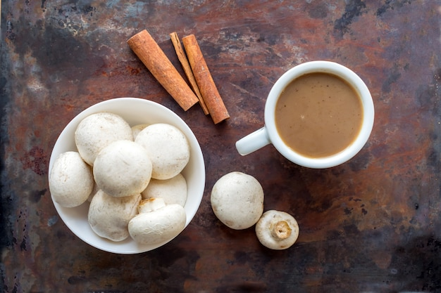 Mushroom coffee superfood trend. cup of coffee and white bowl with mushrooms Premium Photo