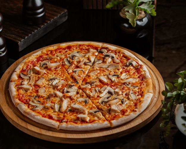 Mushroom pizza with tomato sauce and served in a round bamboo board Free Photo
