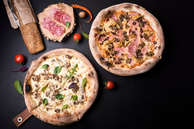 Mushroom and salami pizza with ingredients arranged over black surface Free Photo