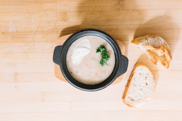 Mushroom soup with bread slices on wooden textured background Free Photo