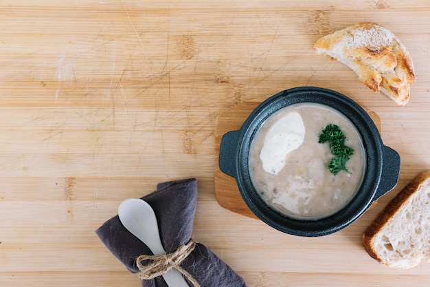 Mushroom soup with bread; tablecloth and spoon on wooden backdrop Free Photo