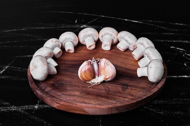 Грибы на деревянной тарелке с зубчиком чеснока Бесплатные Фотографии