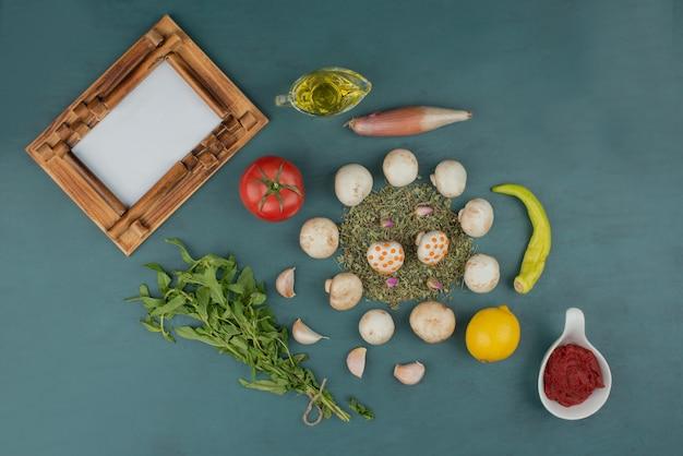 キノコ、レモン、ペパーミント、ミント、トマト、油を額縁付きの青いテーブルに。 無料写真