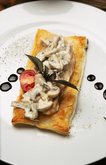 Mushtoom sauteed, chicken stroganoff on a piece of bread. antipasta in a decorated white plate with cutlery on wooden table Free Photo