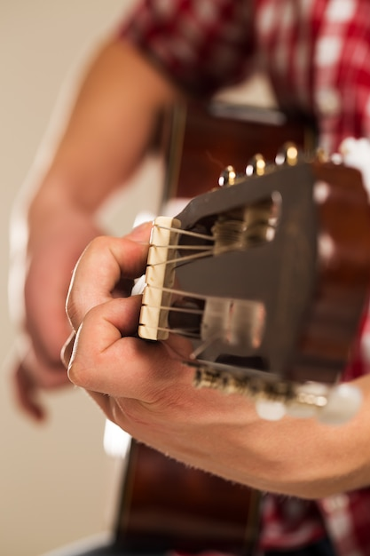 Music, close-up. musician holding a wooden guitar Free Photo