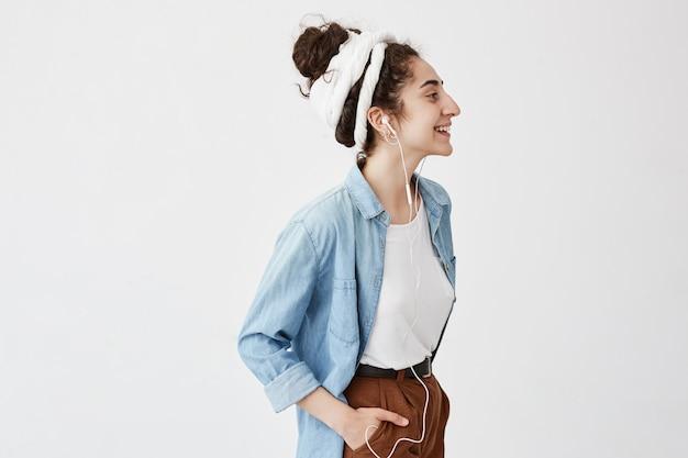 음악, 행복 및 기술. 사랑스러운 세련된 소녀 Hairbun, 갈색 바지의 주머니에 손을 보유하고 휴대 전화에서 음악을 듣고, 광고 복사 공간 흰색 벽에 포즈 무료 사진