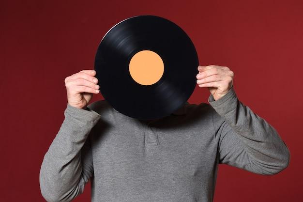 Музыкальная пластинка закрывает лицо на красном фоне Premium Фотографии