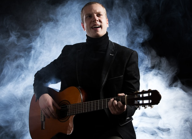 Music. young musician in black suit holding a guitar Free Photo