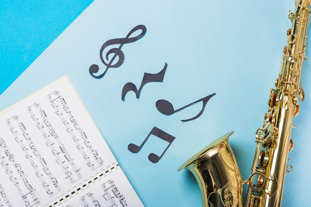 Musical notebook and golden saxophones on blue backdrop Free Photo