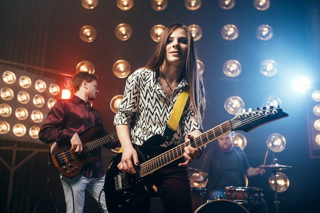 Musical performers on the stage in night club, vintage style. guitarists and drummer, rock band concert, music show Premium Photo