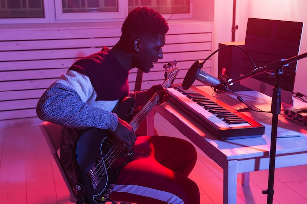 ミュージシャンと音楽のコンセプトを作る-レコーディングスタジオで働くアフリカ系アメリカ人の男性サウンドプロデューサー。 Premium写真