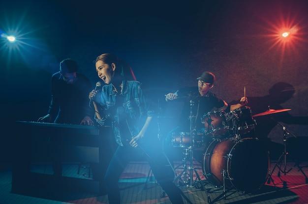 マイクを持って歌を歌い、felloで楽器を演奏するミュージシャンのバンドの手 Premium写真