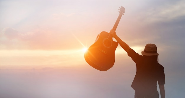 Musician holding acoustic guitar in hand on sunset Premium Photo