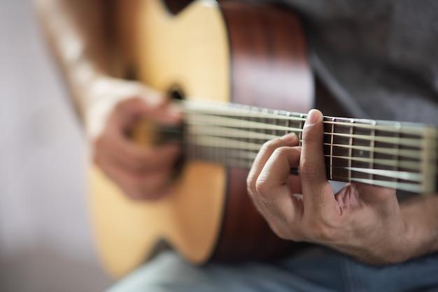 Musician man playing acoustic guitar Premium Photo