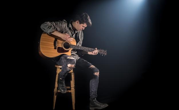 Музыкант играет на акустической гитаре, сидя на высоком стуле, черный фон с красивым мягким светом Бесплатные Фотографии
