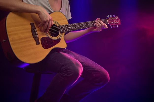 The musician plays an acoustic guitar. Free Photo