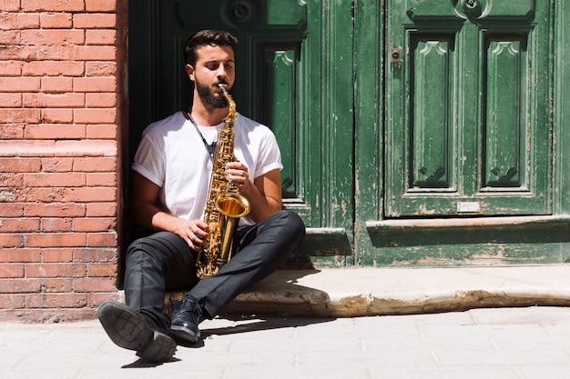 Musician sitting and playing the saxophone Free Photo