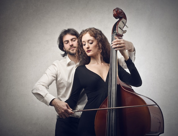 Musician teaches student to play on a contrabass Premium Photo