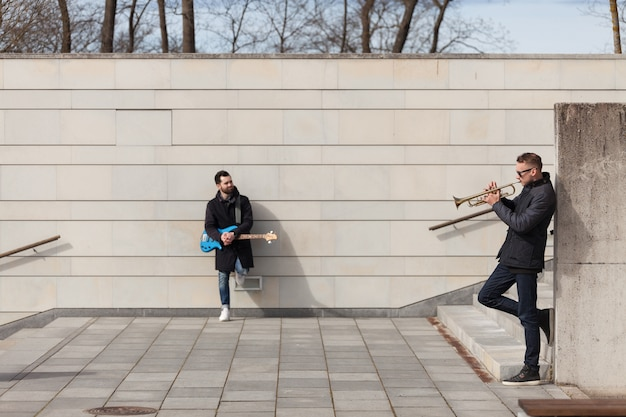 Musicians leaning on wall and playing Free Photo