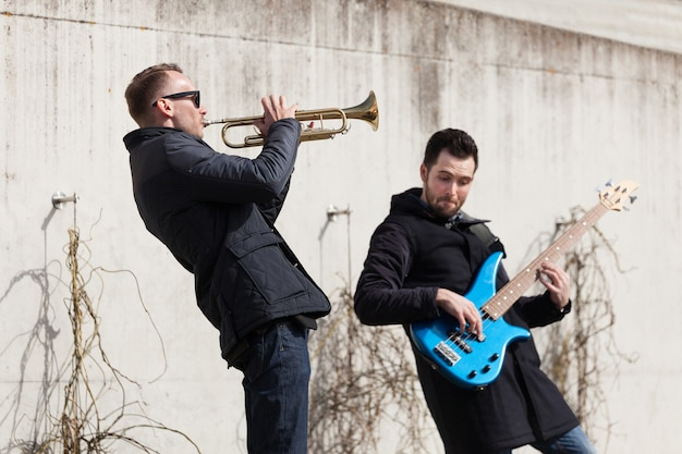 Musicians playing in front of a concrete wall Free Photo