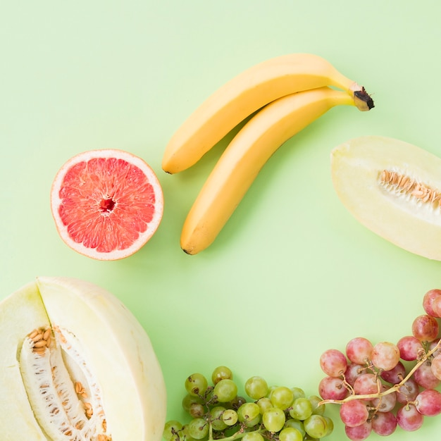 Muskmelon; halved grapefruit; banana; red and green grapes on colored background Free Photo