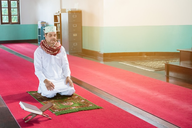Muslim arab businessman sit on his knees with white hijab dress Premium Photo