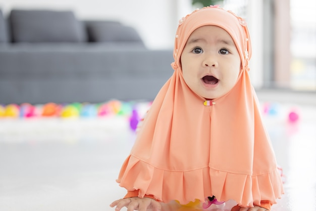 Muslim baby plays with colorful toys in the living room Premium Photo
