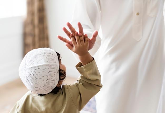 Muslim boy giving a high five Premium Photo