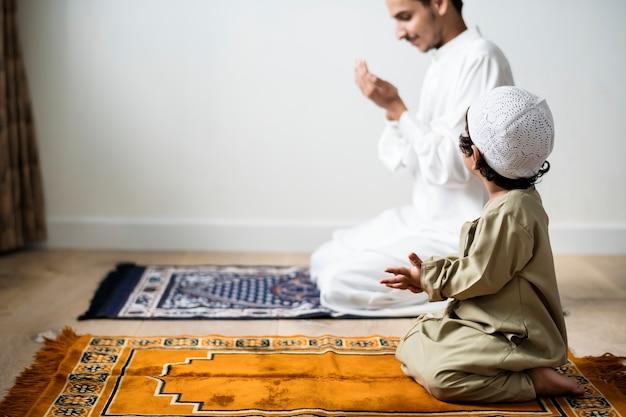 Muslim boy learning how to make dua to allah Premium Photo