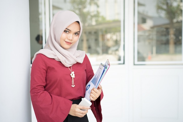 Muslim business woman holding a report and mobile phone. Premium Photo
