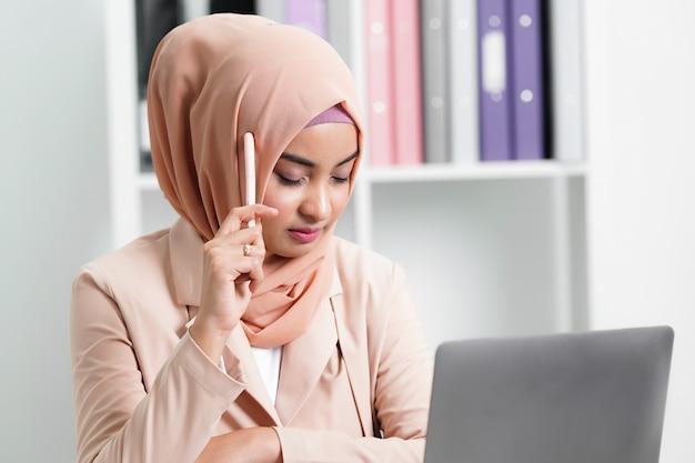 이슬람 비즈니스 여자는 사무실에서 일과 아이디어에 대해 생각하고 있습니다. 프리미엄 사진
