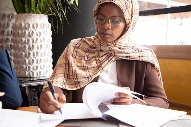 Muslim businesswoman scanning contract Free Photo