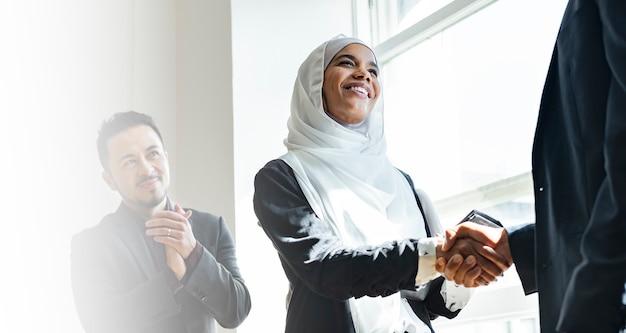 Деловая женщина-мусульманка, пожимая руки для заключения делового соглашения Бесплатные Фотографии