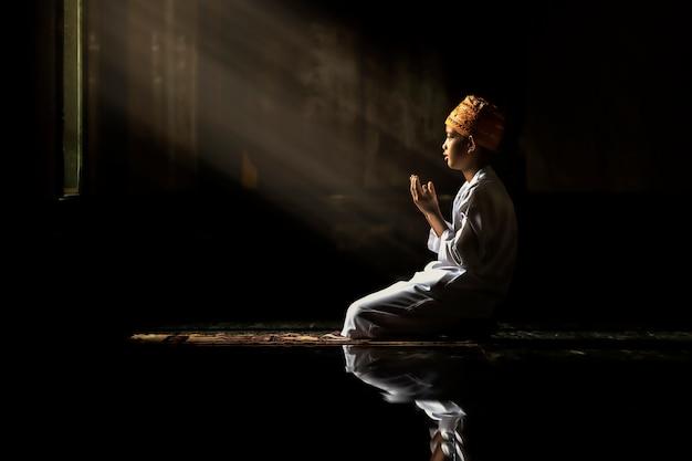 Anak muslim anak laki-laki berkemeja putih mengerjakan buku bacaan doa Foto Premium