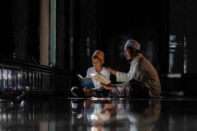 Muslim children kid and old man teaching wearing white shirts doing prayer reading book Premium Photo