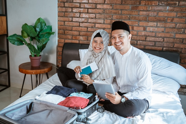 パスポートとタブレットを保持しているイスラム教徒のカップル Premium写真